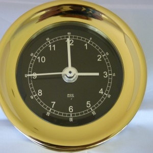 Brass clock black dial face